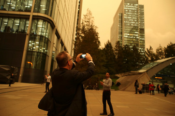 A man photographs the sky turning red over buildings in Canary Wharf as dust from the Sahara carried by storm Ophelia filters sunlight over London