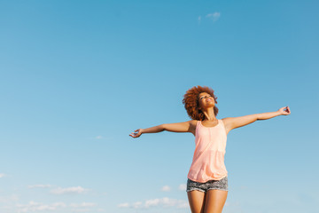 Latin American Afro Woman with Arms Wide Open in a Radiant Summer Day