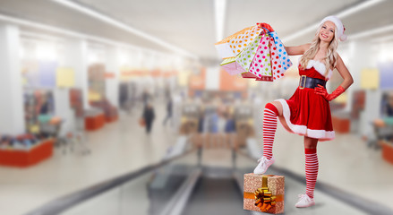 A girl in Santa Claus costume with a package of gifts on the background of the trading center.