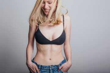 Sexy blonde woman in jeans and black bra.