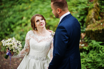 Close-up photo of a wedding couple looking each other in the eyes in nature.