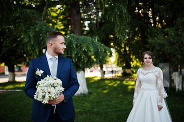 Wonderful young wedding couple posing outdoor on a gorgeous sunny spring day.