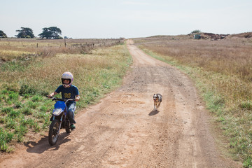 Farmkid riding his trail bike on the farm with his dog alongside