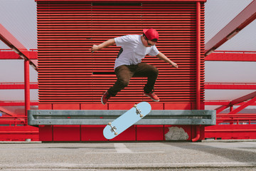 teenager doing a kickflip with his skateboard in red modern urban area