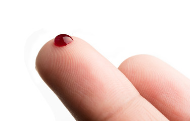 Drop of blood on finger on white background