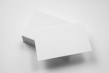 Stack of blank business card with one card in front on white background