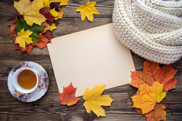 Autumn picture of yellow leaves, a cup of tea, a scarf and a piece of paper on wood background