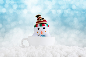 Merry christmas and happy new year background. Snowman in cup with winter background.