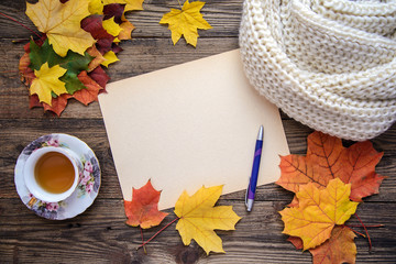 Autumn picture of yellow leaves, a cup of tea, a scarf and a piece of paper with pen on wooden background