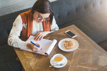 Young businesswoman in glasses and white sweater is sitting in cafe at table, signing documents. Student is studying online, doing homework. On table cup of tea, cookies, smartphone. E-learning.