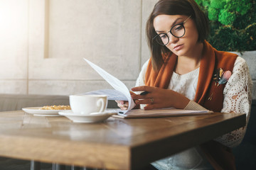 Front view.Young businesswoman is sitting in coffee shop at table,reading documents.Student is studying online, doing homework.On table cup of tea, cookies. E-learning, education. Freelancer working.