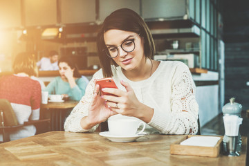 Young businesswoman in glasses and white sweater is sitting in cafe at table and using smartphone, working. Student is studying online, e-learning. Online marketing, education. Hipster girl chatting.