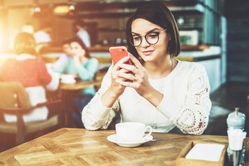 Young businesswoman in glasses and white sweater is sitting in cafe at table and using smartphone, working.E-learning,online marketing,education.Hipster girl looking on screen of phone,checking email.