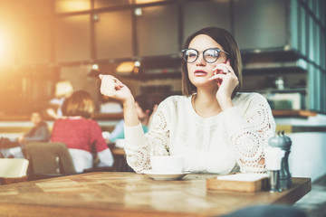Young serious businesswoman in glasses sitting in cafe at wooden table and talking on cell phone. Telephone conversations. Hipster girl freelancer discusses working questions over phone. Girl calling.