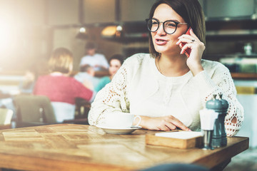 Young businesswoman in glasses and white sweater is sitting in cafe at wooden table and talking on cell phone.Telephone conversations.Hipster girl is talking on phone with her friend.Instagram filter.