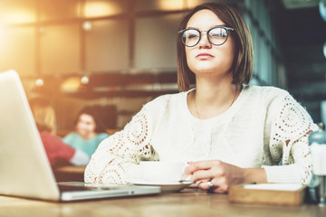 Young businesswoman in glasses is sitting in cafe at table in front of laptop. Student is studying online.Online education, marketing, e-learning. Social media, network. Instagram filter, film effect.
