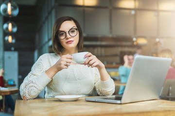Young businesswoman sitting in cafe at table,drinking tea and working on laptop.Student is studying online.Hipster girl using computer.Online education, marketing, e-learning.Social media, network.
