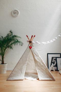 Cute handmade teepee in a room.