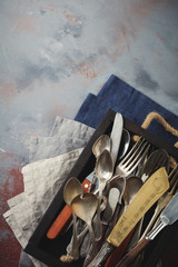 Vintage forks, spoons and knives in a dark old wooden box on a gray concrete or stone background. Selective focus.Top view. Copy space..