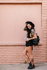 A woman standing in a coral pink alley way with a backpack & mobile phone