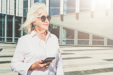 Summer sunny day.Middle-aged woman,retired woman dressed in white shirt and sunglasses,stands on city street,holds smartphone and listening music in headphones. In background is modern glass building.