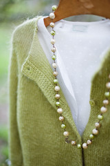 Ancient pearls necklace, cardigan and shirt on coat hanger