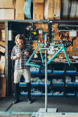 Young Bicycle Mechanic Assembling Fixed Gear Bike in Bright Workshop