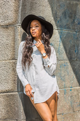 Young Mixed Race American Woman with long hair relaxing outside in New York, wearing white striped shirt, black sun hat, wristwatch, holding sunglasses, standing against wall on street under sun..