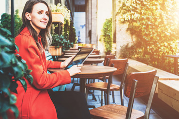 Side view.Young smiling attractive woman in orange coat is sitting outside in cafe at table and uses tablet computer. Girl checking email, blogging, chatting, reading e-book.Social media, e-learning.