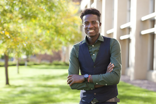 Handsome confident young black student man smiles on college campus