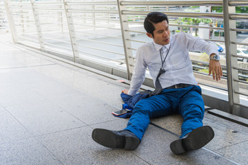 Tired or stressed businessman sitting on the walkway after was fired from company. concept of business failure and unemployment problem