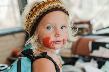Fierce little girl covered in red paint