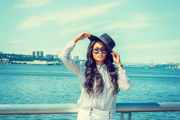 Young American Woman with long hair traveling in New York in summer, wearing white striped shirt, black sun hat, sunglasses, standing by Hudson River, hands touching hat. Bridge, harbor on background.