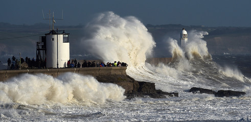 Waves crash over the lighthouse as storm Ophelia passes Porthcawl, Wales