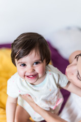 Cheerful baby playing with her mother