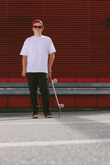 male teenager with skateboard in front of red background