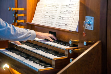 Close up view of a organist playing a pipe organ