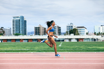 Young african american female sprinter running on an athletics track.