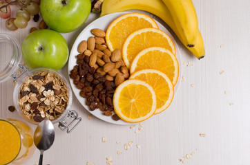 Healthy food. Fruit, homemade granola, nuts, orange juice on a white table