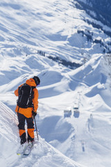 Skier standing on steep mountain slope
