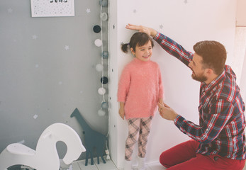 Father is measuring his baby height on the wall. Cute little daughter and her handsome young dad are playing together in child's room.