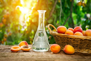 Fruit brandy in a bottle and apricots