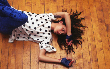 Young woman lying on the floor in a t-shirt with polka dots