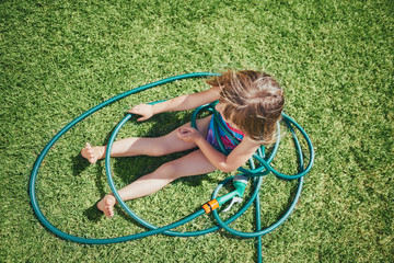 cute little girl tangled up in a hose pipe