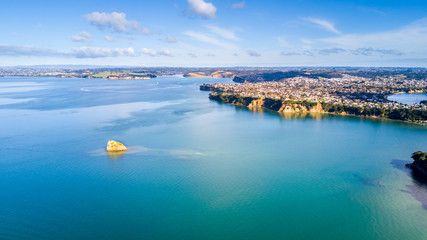 Aerial view on residential suburbs surrounded by sunny ocean harbour. Whangaparoa peninsula, Auckland, New Zealand.