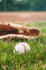 Close-up of baseball in grass near mitt