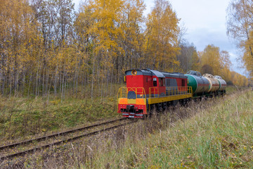 old locomotive with tanks in the autumn forest