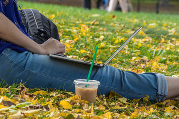 Young woman, college student dressed in blue shirt is studying outdoor with beautiful fall foliage