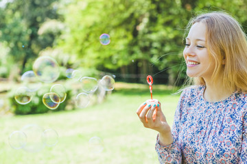 Cute Teen Girl Playing with Bubbles in a Park
