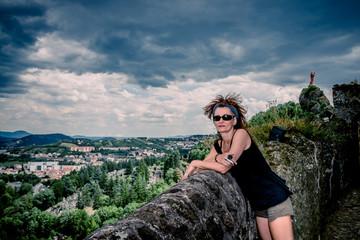 Femme en haut du rocher Saint-Michel d'Aiguilhe  au Puy-en-Velay pendant un orage
